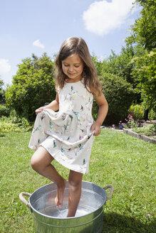 Girl taking a footbath in zinc bucket - RBF003221