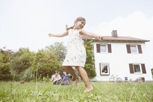 Playful girl with parents in garden - RBF003224