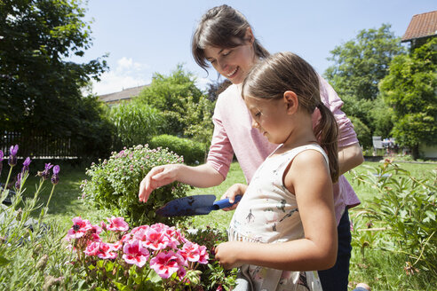 Smiling mother and daughter in garden planting flowers - RBF003226