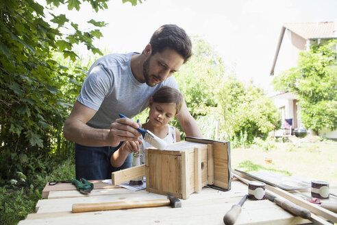 Father and daughter painting a birdhouse - RBF003231