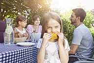 Girl eating a corn cob on a family barbecue in garden - RBF003250