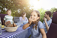Girl eating bread with family at garden table - RBF003219