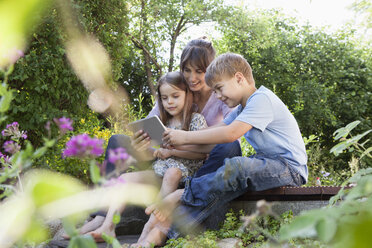 Mother, son and daughter with digital tablet in garden - RBF003256