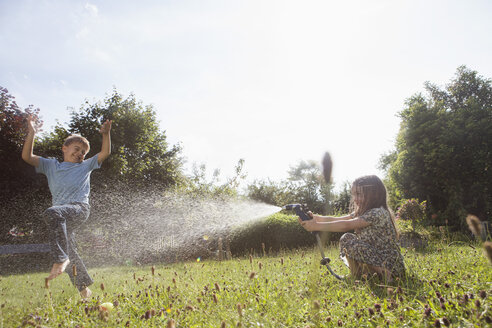 Boy and girl splashing with water in garden - RBF003259