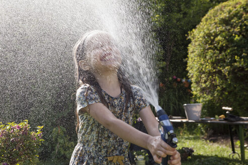 Girl splashing with water in garden - RBF003262