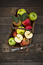 Different apples, basket and pocket knife on wood - LVF003844