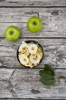 Bowl of apple chips, leaves and two Granny Smith on wood - LVF003856
