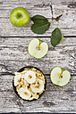 Bowl of apple chips, leaves and whole and sliced Granny Smith on wood - LVF003859