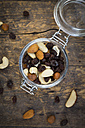 Mixed nuts and raisins in glass on wood - LVF003880