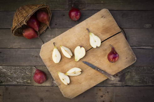 Whole and sliced organic red Clapp's Favourites, wooden board and kitchen knife on dark wood - LVF003902