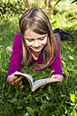 Happy little girl lying on a meadow in the garden reading a book - SARF002112