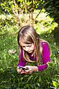 Little girl lying on a meadow in the garden looking at smartphone - SARF002118