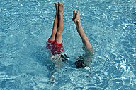Teenage boy and girl doing a handstand in swimming pool - LBF001205