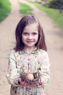 Smiling girl holding an egg in a nest - XCF000028