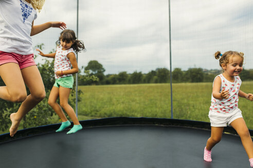 Three girls bouncing on trampoline - MGOF000796