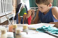 Boy painting nativity figurines - SKCF000014