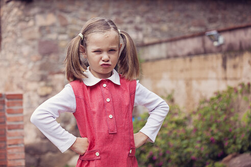 Portrait of little girl with hands on her hips pouting mouth - XCF000033