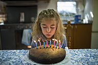 Little girl blowing out candles on her birthday cake - RAEF000505