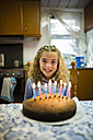 Portrait of happy little girl with birthday cake at home - RAEF000508