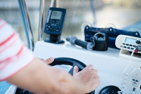 Hands at the steering wheel of a fishing boat with fish finder, GPS , compass and VHF radio - ABAF001928