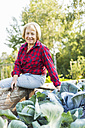 Smiling senior woman at vegetable patch - UUF005729