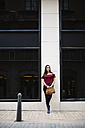 Young woman in the city leaning against a wall - JRFF000084