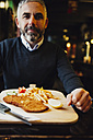 Man in restaurant having Wiener Schnitzel with French fries - AIF000089