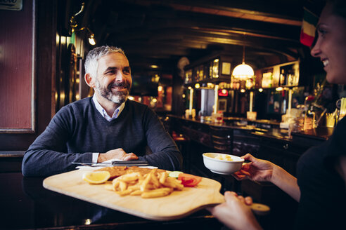 Smiling man in restaurant receiving Wiener Schnitzel with French fries - AIF000092