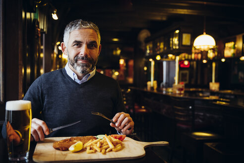 Smiling man in restaurant having Wiener Schnitzel with French fries - AIF000095