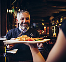Smiling man in restaurant receiving Wiener Schnitzel with French fries - AIF000098