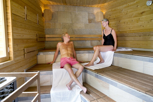 Senior couple relaxing in textile sauna - TOYF001406