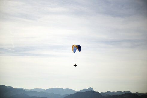 Austria, Tyrol, paraglider in front of cloudy sky - JED000244