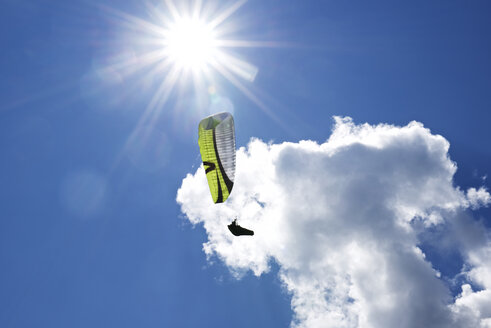 Austria, Tyrol, paraglider in front of a cloud seen from below - JED000247