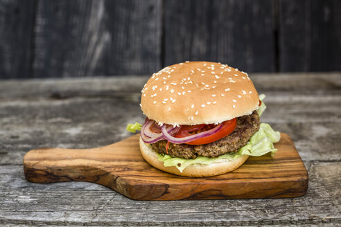 Homemade burger with lettuce, meat, tomato and onion on chopping board - SARF002133