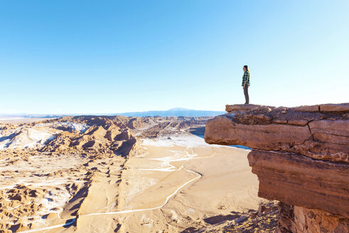 Chile, Atacama Desert, woman standing on a cliff looking at view - GEMF000394