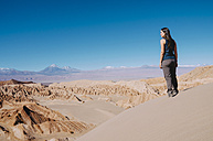 Chile, Atacama Desert, woman standing on a dune looking at view - GEMF000397
