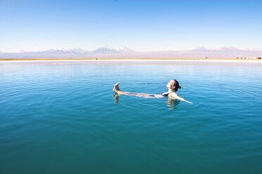 Chile, Atacama Desert, woman floating in the Laguna Cejar salt lake - GEMF000403
