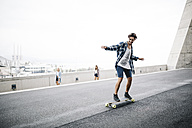 Young man balancing on longboard, girls watching - JRFF000097