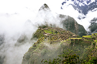 Peru, Machu Picchu region, Machu Picchu citadel and Huayna mountain in fog - GEMF000414