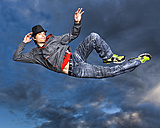 Young man jumping in the air in front of evening sky - STSF000937