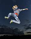 Young man jumping in the air in front of evening sky - STSF000940