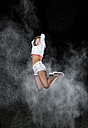 Young woman jumping in between cloud of flour in front of night sky - STSF000943