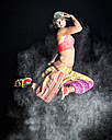 Young woman jumping in between cloud of flour in front of night sky - STSF000946