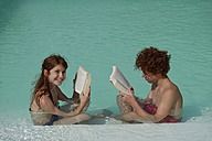 Redheaded girl and boy sitting at  pool edge reading a book - LBF001223