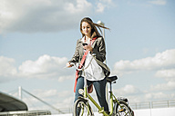 Young woman with bicycle looking at cell phone - UUF005768