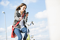 Young woman on bicycle looking at cell phone - UUF005774