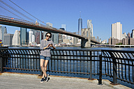 USA, New York City, portrait of  young woman hearing music with headphones in front of skyline - GIOF000132