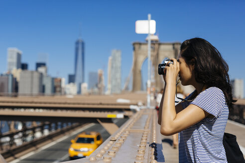 USA, New York City, young woman standing on Brooklyn Bridge taking a photo with camera - GIOF000135