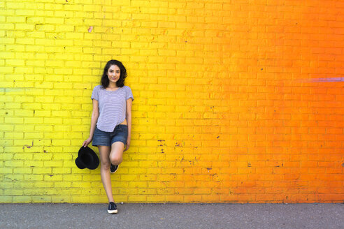 Portrait of smiling young woman leaning against yellow brick wall - GIOF000141