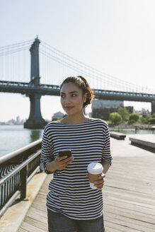 USA, New York City, portrait of smiling young woman with smartphone and coffee to go - GIOF000144
